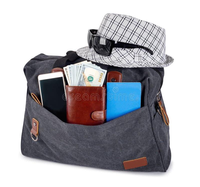 Gro?e schwarze stilvolle Reisetasche f?r Reise mit Hut, P?ssen und Geld auf wei?em Hintergrund lizenzfreies stockbild