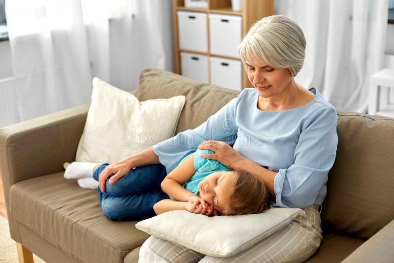 Gro?mutter und Enkelin, die auf Kissen schlafen stockfotografie