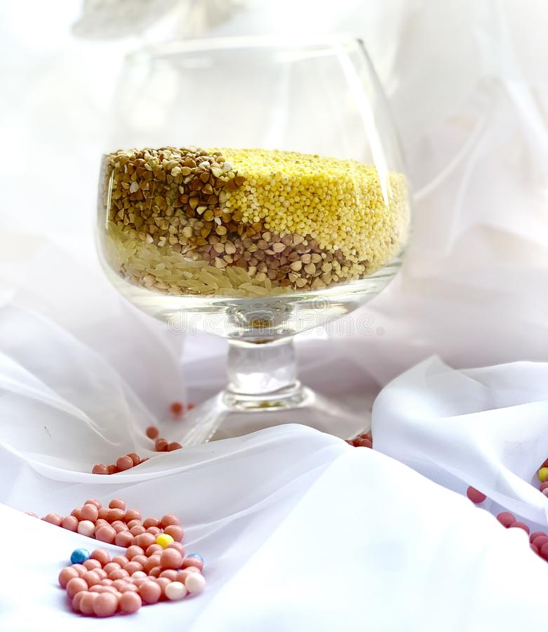 Groats in a glass, white rice, yellow millet, brown buckwheat. Beautiful color combination, on a white background. royalty free stock photography
