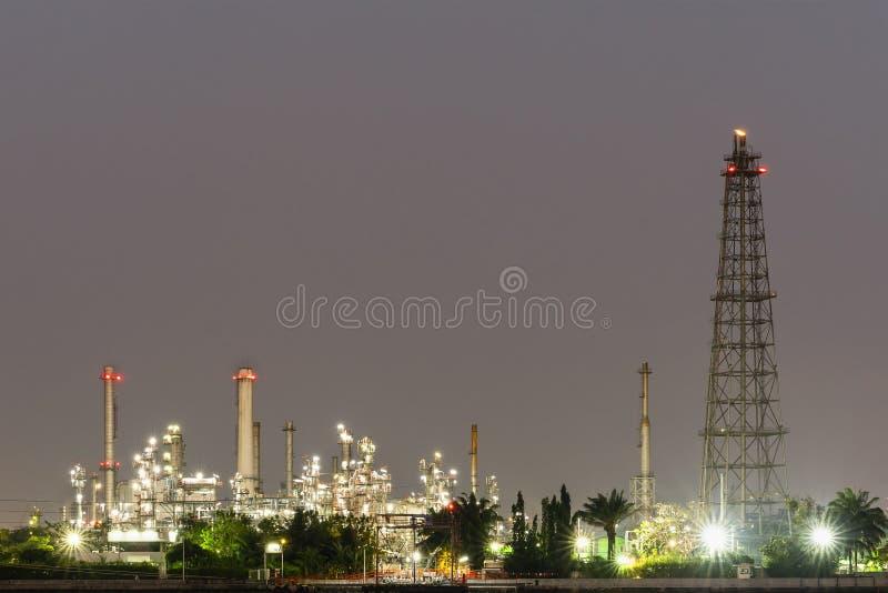 Grobe Erdölraffinerieanlage des Nachtfotos und viel Kamin an der Küste des Flusses mit buntem hellem Licht von der Lampe bei Thai lizenzfreies stockbild