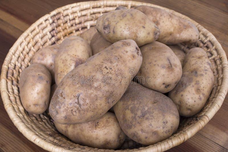 Grobe Kartoffeln in gesponnenem Korb lizenzfreies stockbild