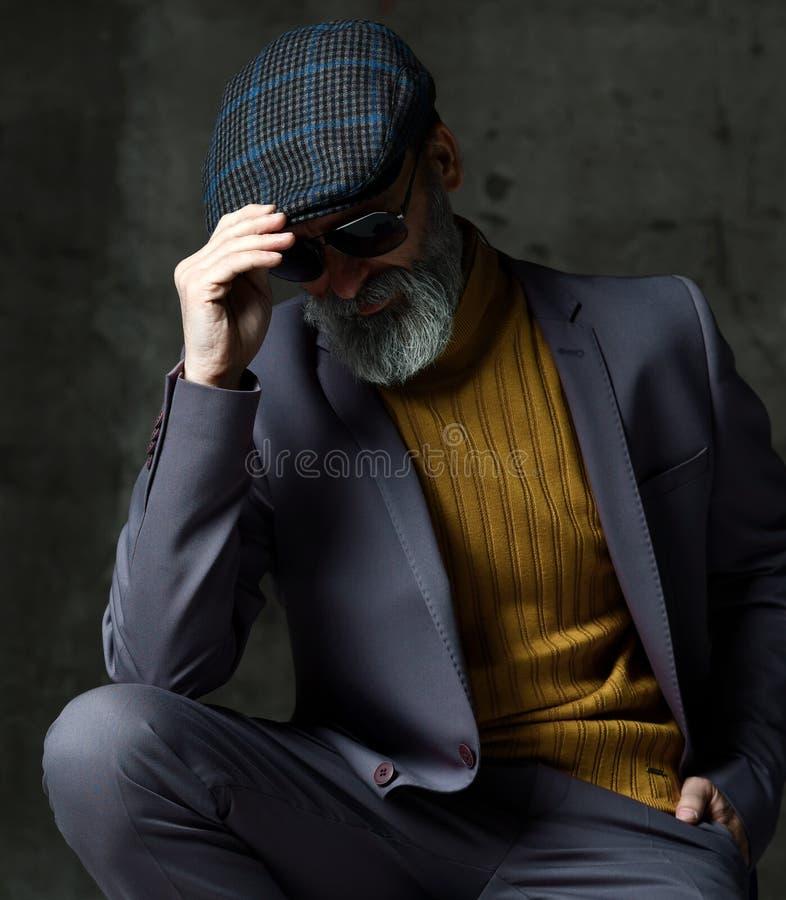 Grober älterer weißer bärtiger Mann in der klassischen grauen Klage, grüne stilvolle moderne Männer der Strickjacken-, Kappen- un stockfotos
