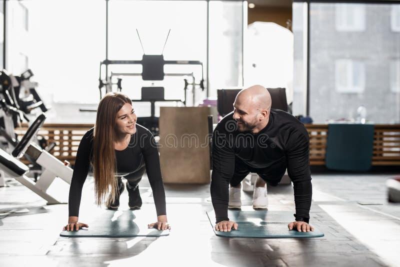 Grober athletischer Mann und junge schlanke das Mädchen, die in der schwarzen Artkleidung gekleidet wird, tun Planke in der moder stockfotos
