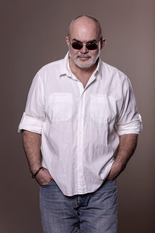 Grober kahler älterer Mann im Hemd, in den Jeans und in der Sonnenbrille lizenzfreie stockfotos
