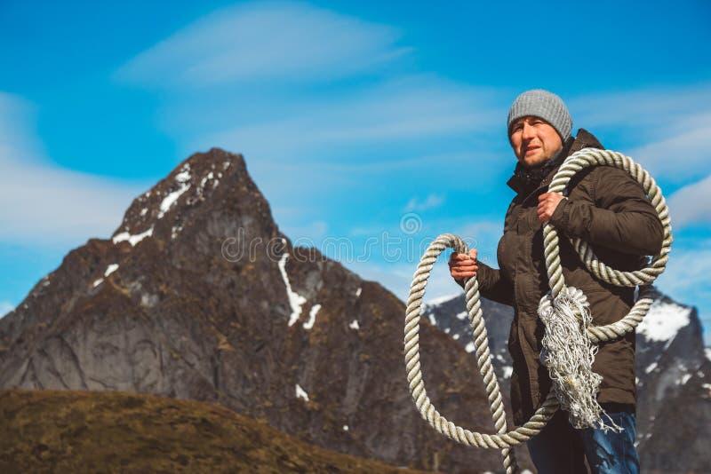 Grober Mann mit einem Seil auf seiner Schulter vor dem hintergrund der Berge und des blauen Himmels Kopieren Sie Platz Kann wie v stockfoto