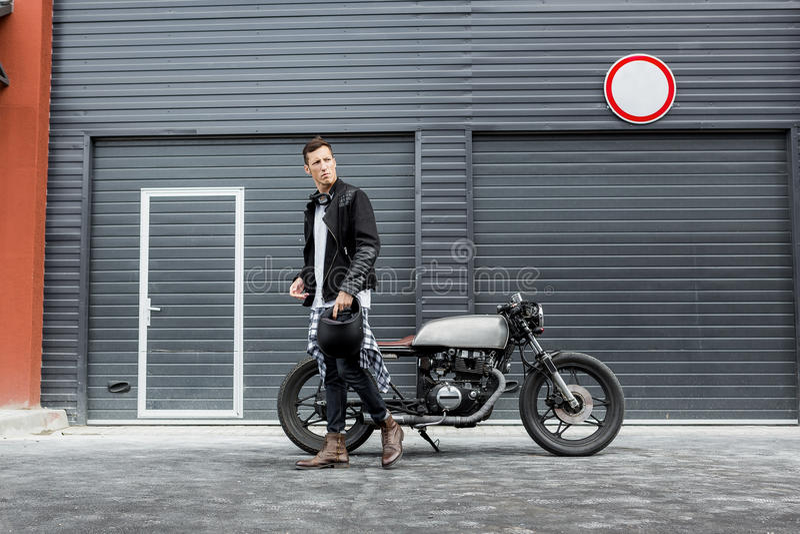 Grober Mann nahe seinem Caférennläufer-Gewohnheitsmotorrad stockfoto