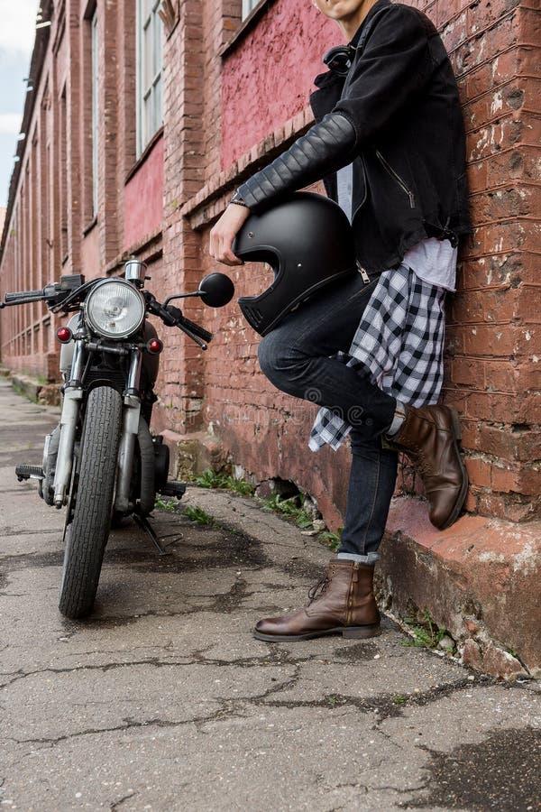 Grober Mann nahe seinem Caférennläufer-Gewohnheitsmotorrad lizenzfreies stockfoto