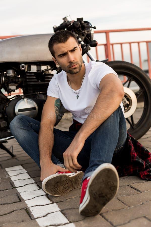 Grober Mann nahe seinem Caférennläufer-Gewohnheitsmotorrad stockbild