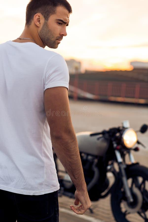 Grober Mann nahe seinem Caférennläufer-Gewohnheitsmotorrad lizenzfreie stockbilder