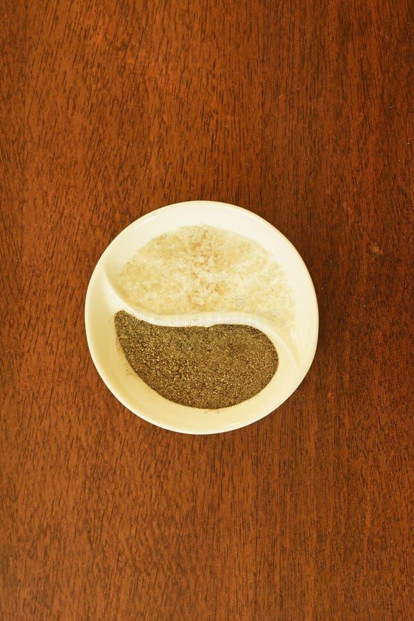 Grobes Salz und Boden pfeffert in kleiner Untertasse Ying und Yangs lizenzfreie stockfotografie