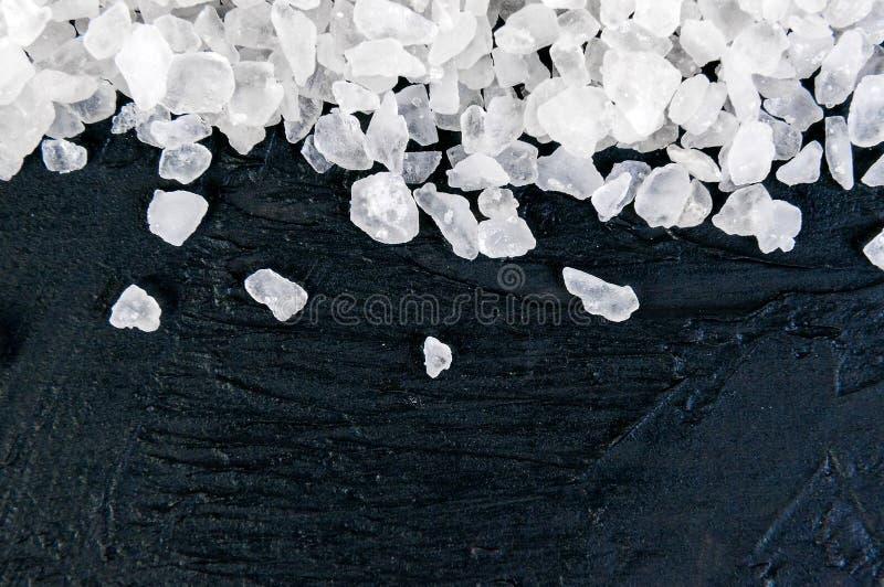 Grobes Seesalz auf schwarzem Schiefersteinhintergrund, Nahaufnahme, freier Raum für Ihren Text lizenzfreie stockbilder
