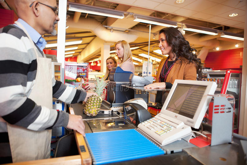 Grocer Store Checkout. Shop assistant with customer in supermarket royalty free stock photography