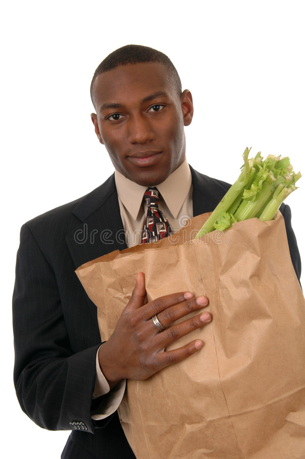 Groceries. A man in a suit carrying a bag of groceries stock image
