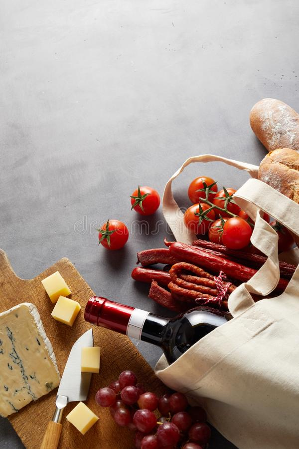Groceries for a pub style lunch. With red wine in a natural fiber reusable shopping bag to reduce use of plastic stock image