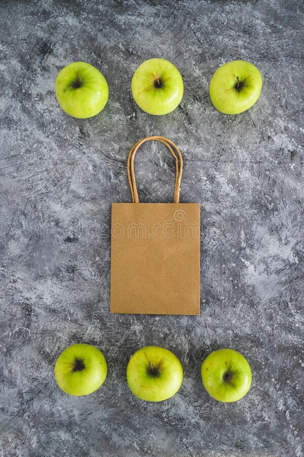 Groceries shopping concept, shopping bag among apples symbol of healthy nutrition. Home delivery and groceries shopping concept, shopping bag among apples symbol royalty free stock image