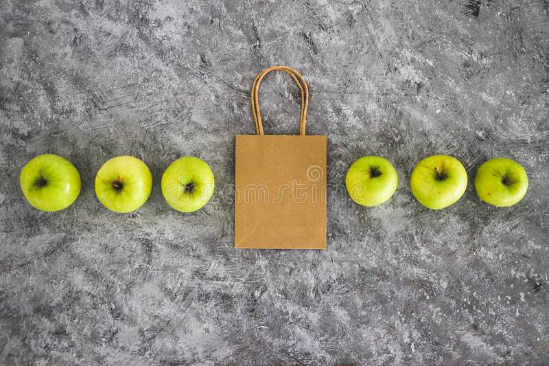 Groceries shopping concept, shopping bag among apples symbol of healthy nutrition. Home delivery and groceries shopping concept, shopping bag among apples symbol stock image