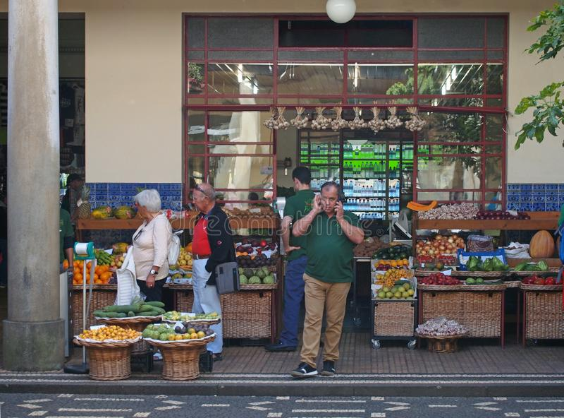 Grocers outside a shop selling fruit and vegetables in funchal market in madeira with produce arranged in baskets outside royalty free stock images