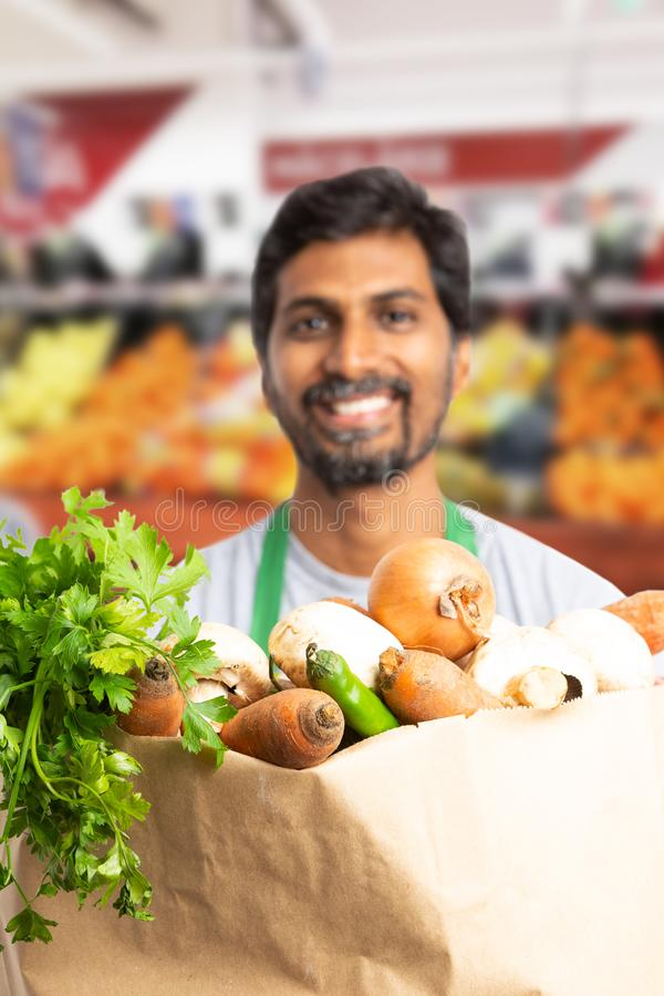 Grocery bag presented by indian employee royalty free stock images
