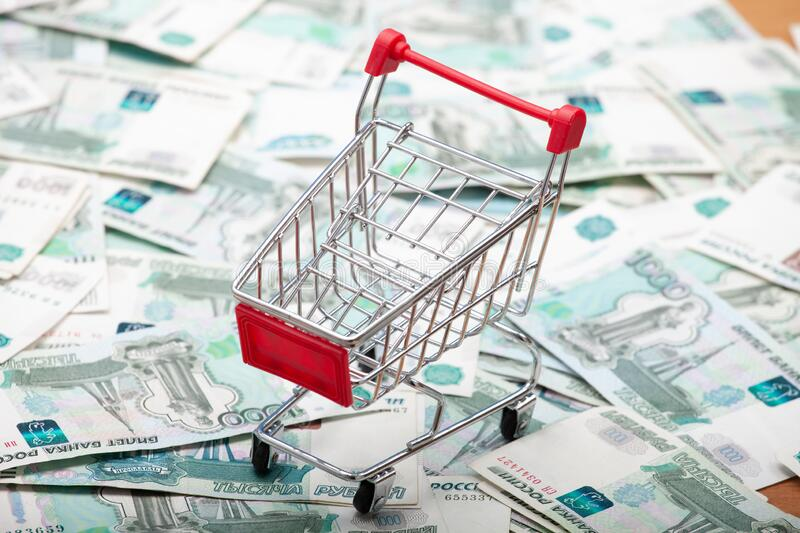 grocery cart with a red handle on the background of 1000 ruble banknotes. royalty free stock photo