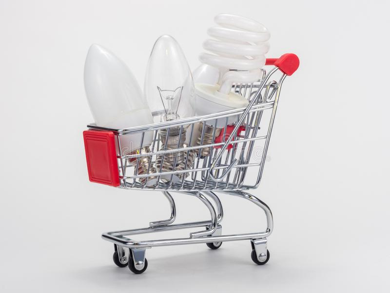 In the grocery cart are three light bulbs: incandescent, energy-saving and LED royalty free stock photos
