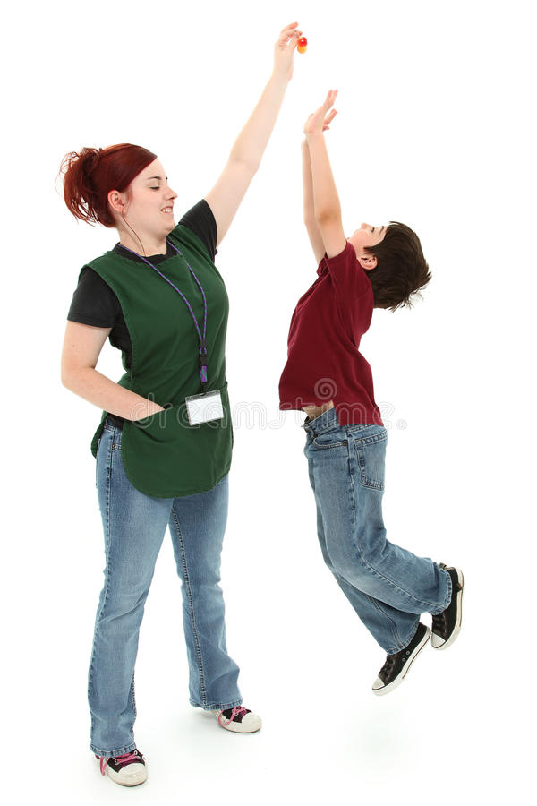 Grocery Clerk and Excited Boy. Attractive 19 year old grocery clerk woman holding cherries away from hungry jumping 8 year old boy child over white. Full length stock image