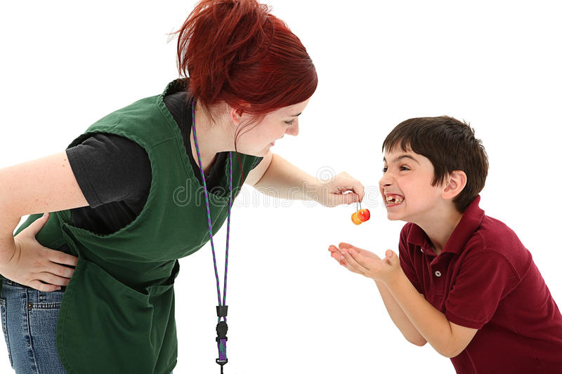 Grocery Clerk and Excited Boy. Attractive redhead 19 year old grocer clerk sharing cherries with 8 year old french boy making funny faces over white background royalty free stock photos