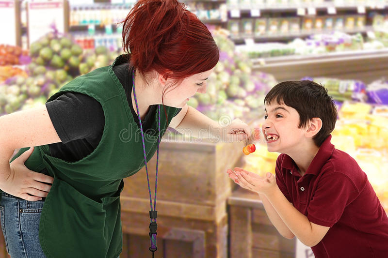 Grocery Clerk Giving Child Cherries in Store. Attractive young grocery clerk sharing fresh cherries with child customer in grocery store royalty free stock photography