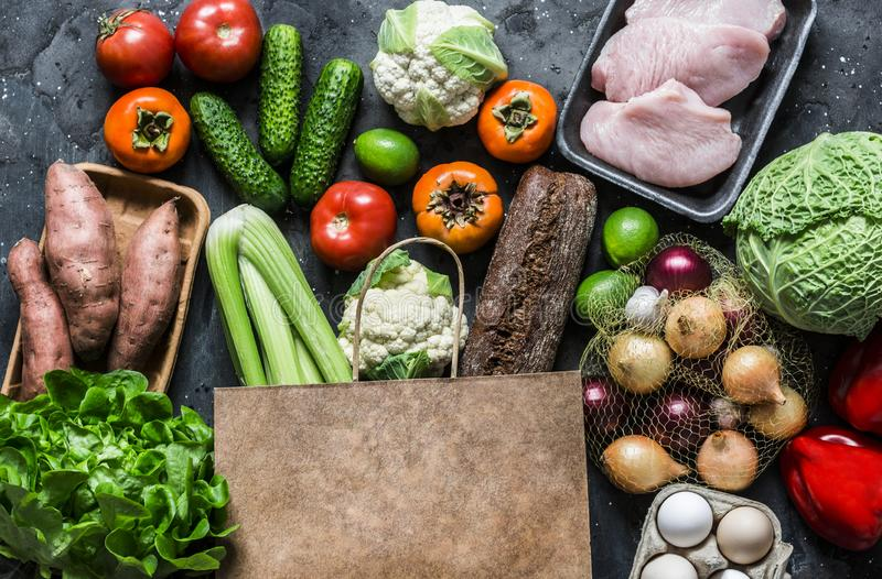 Grocery paper bag with fresh organic vegetables, fruits, meat on a dark background, top view. Healthy diet food concept royalty free stock photography
