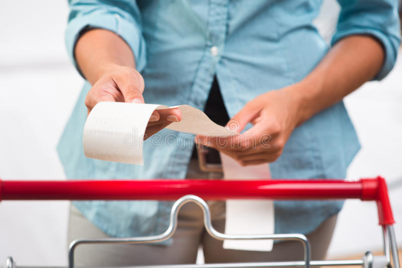 Grocery receipt. Unrecognizable woman in light blue shirt checking a long grocery receipt at store royalty free stock image