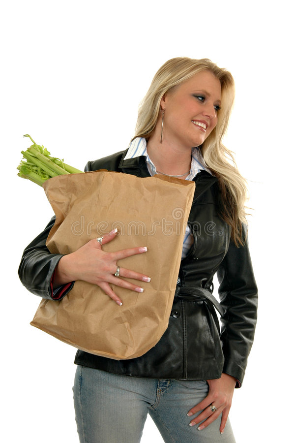 Grocery Shopping. A beautiful woman in a lether jacked carrying a sack of groceries royalty free stock images