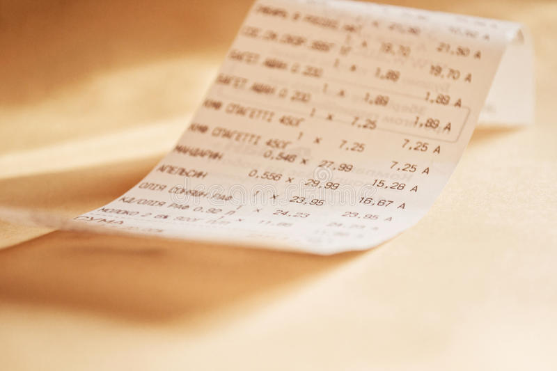 Grocery shopping list. Printed receipt with a list of the goods from the store on a table stock photo