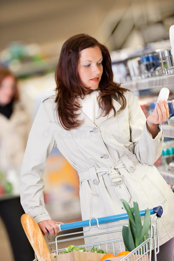 Grocery shopping store - Young brunette woman royalty free stock photo