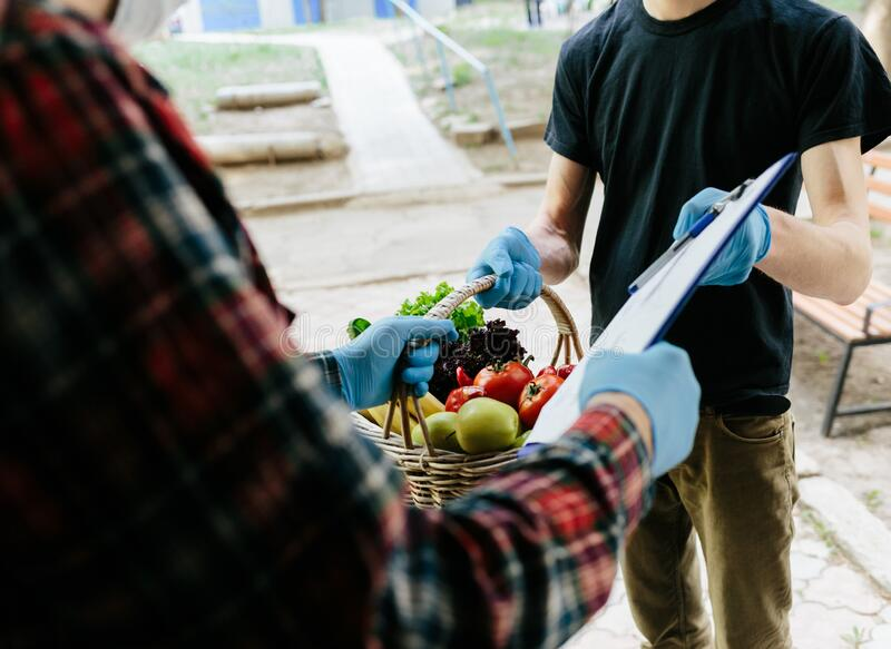 A grocery store delivery man wearing a black polo-shirt delivering food to an old man at home royalty free stock image