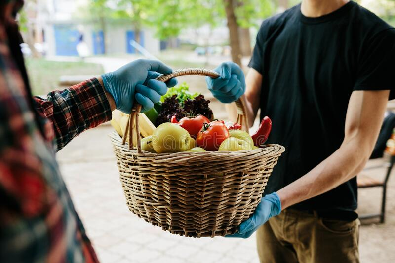 A grocery store delivery man wearing a black polo-shirt delivering food to an old man at home stock images