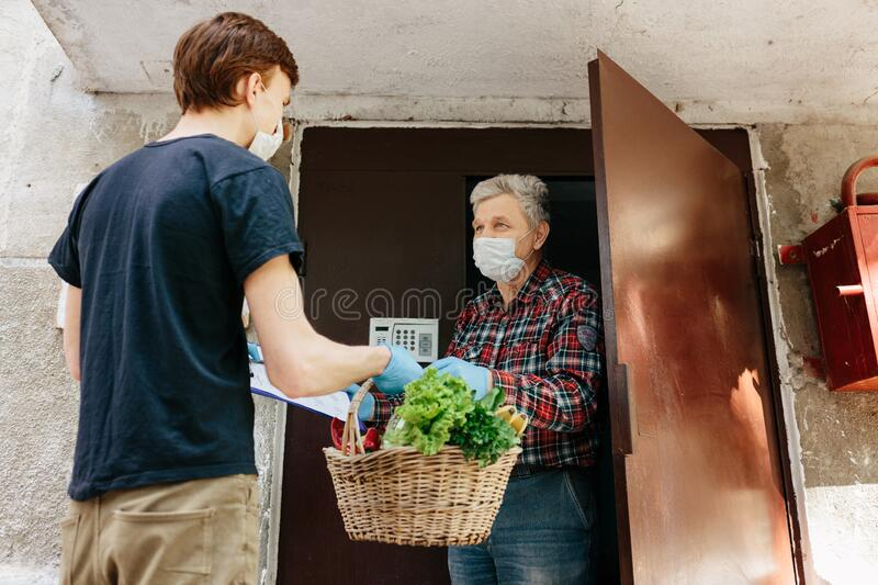 A grocery store delivery man wearing a black polo-shirt delivering food to an old man at home royalty free stock photography