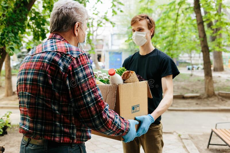 A grocery store delivery man wearing a black polo-shirt delivering food to an old man at home royalty free stock images