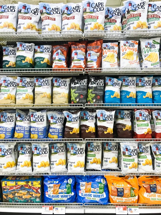 Shelves full of potato chips. A grocery store is full of different styles, sizes and flavors of potato chips royalty free stock image