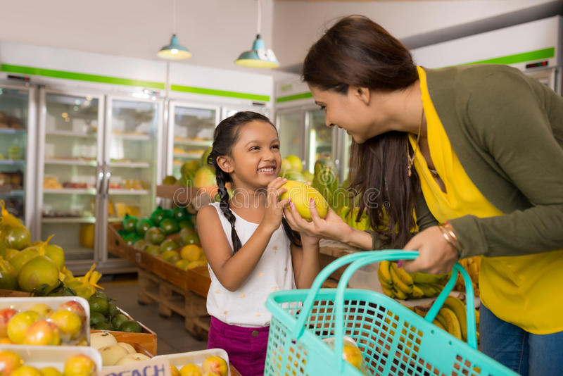 At grocery store. Indian mother and daughter choosing fruits at the grocery store stock photo