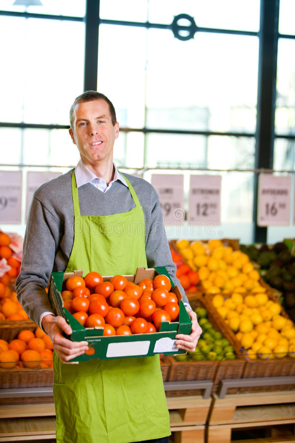 Grocery Store Owner. A friendly grocery store owner with a box of ripe tomatoes royalty free stock images