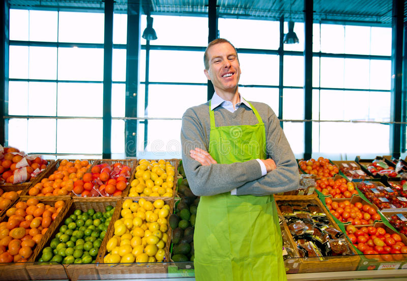 Grocery Store Owner. A grocery store owner standing in front of vegetables and fruit royalty free stock photo