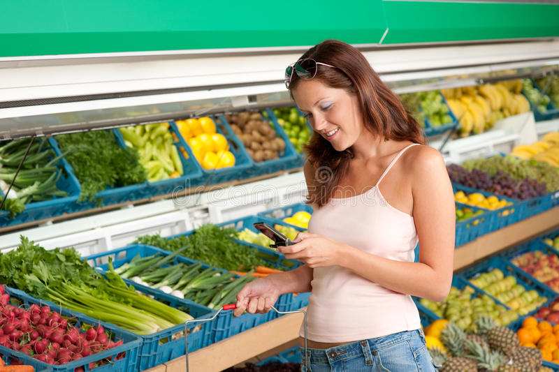 Grocery store - Woman holding mobile phone royalty free stock images