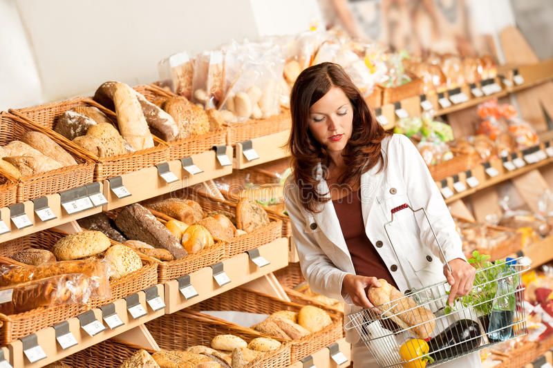 Grocery store: Young woman buying bread stock photos