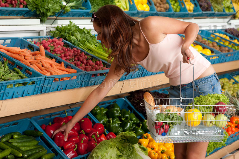Grocery store - Young woman buying vegetable royalty free stock photo