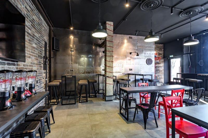 GRODNO, БЕЛАРУСЬ - МАРТ 2019: внутри интерьера в современном баре спорта паба с темным стилем дизайна просторной квартиры с красн стоковые фотографии rf