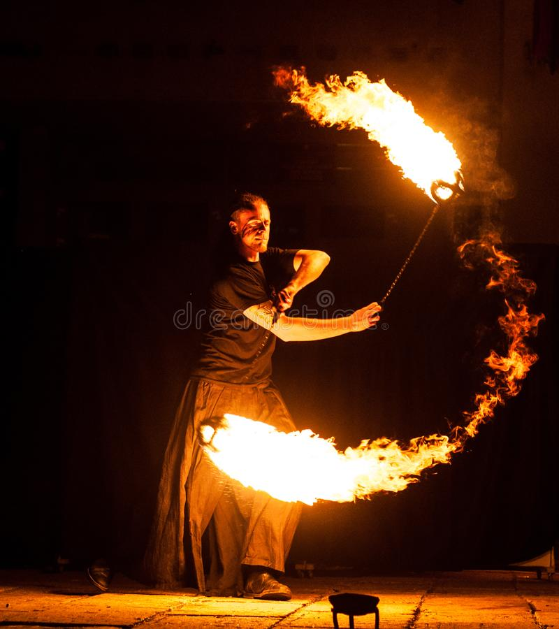 Grodno, Belarus - April, 30, 2012 fire show, dancing with flame, male master fakir juggler with fire works on street arts festival. Fire trick royalty free stock photos