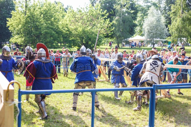 GRODNO, BELARUS - JUNE 2019: group of medieval jousting knight fight, in armor, helmets, chain mail with axes and swords on lists. Historic reconstruction of stock photo