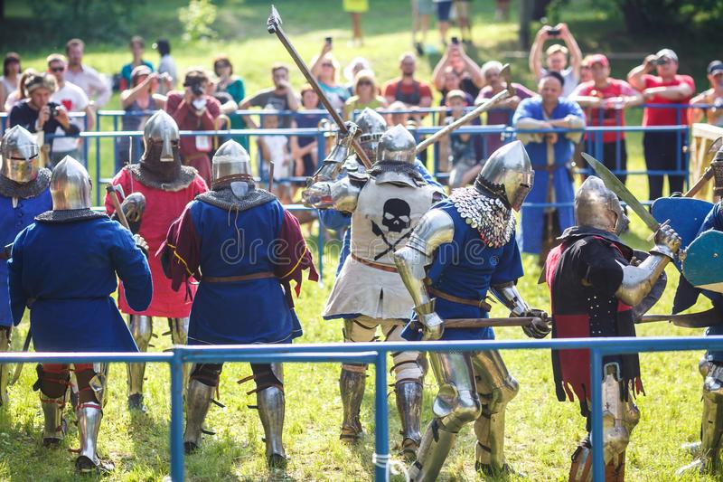 GRODNO, BELARUS - JUNE 2019: group of medieval jousting knight fight, in armor, helmets, chain mail with axes and swords on lists. Historic reconstruction of stock photos