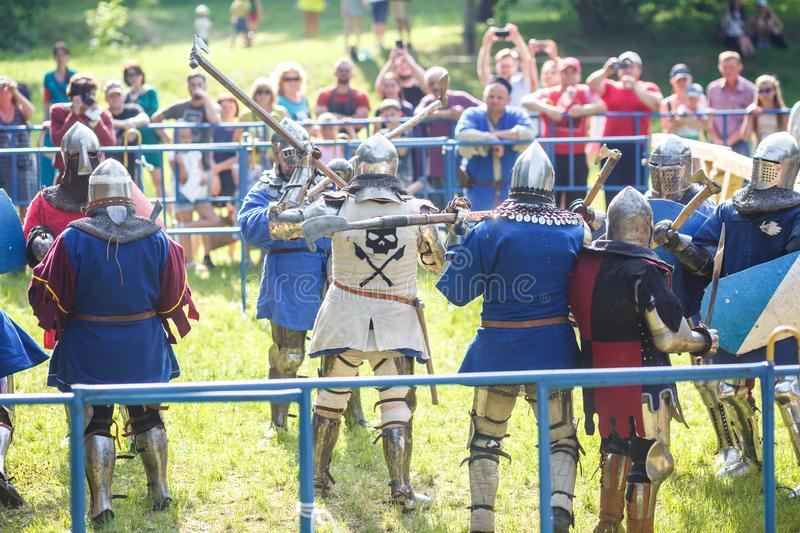 GRODNO, BELARUS - JUNE 2019: group of medieval jousting knight fight, in armor, helmets, chain mail with axes and swords on lists. Historic reconstruction of stock image