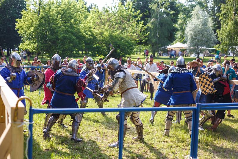 GRODNO, BELARUS - JUNE 2019: group of medieval jousting knight fight, in armor, helmets, chain mail with axes and swords on lists. Historic reconstruction of stock photography
