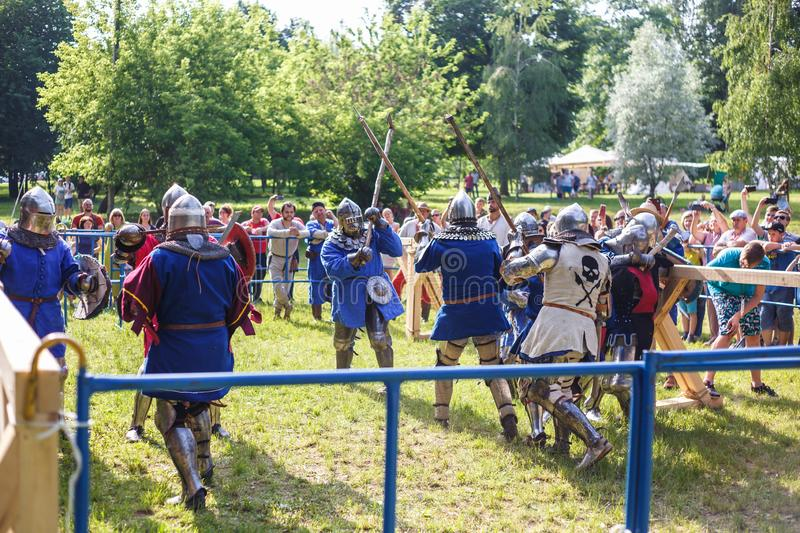 GRODNO, BELARUS - JUNE 2019: group of medieval jousting knight fight, in armor, helmets, chain mail with axes and swords on lists. Historic reconstruction of royalty free stock photo